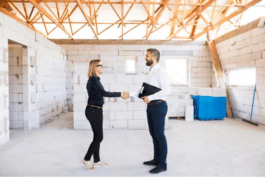 Femme et homme se serant la main sur un chantier